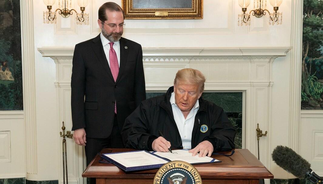 President Donald Trump signerer en lov for finansiering av Corona-respons 6. mars 2020, flankert av helseminister Alex Azar. Trump høres ut som helten som kommer til å klare å slå ned epidemien, mener Denise Gemmellaro, assisterende professor ved Kean University i New Jersey.