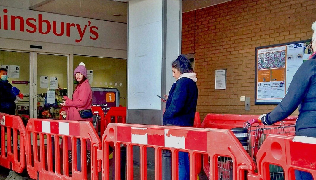 Kunder praktiserer sosial distansering utenfor et supermarked i London