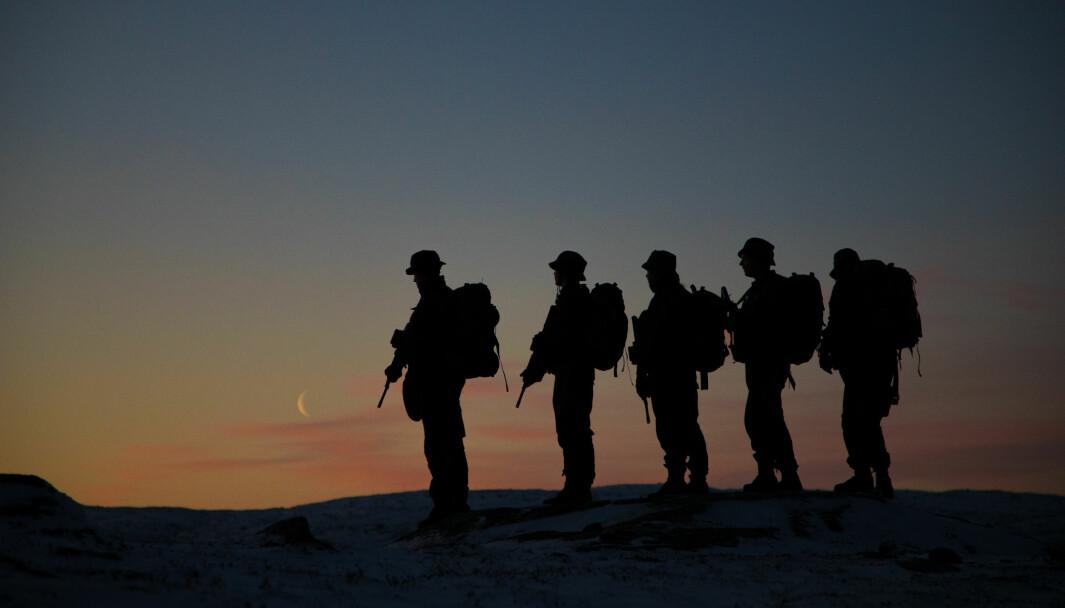 En patrulje fra Garnisonen i Sør-Varanger marsjerer i solnedgang.