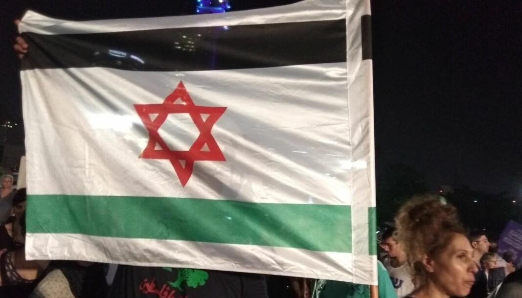 Et flagg kombinerer elementer fra det israelske og det palestinske flagget under en demonstrasjon i Tel Aviv i 2018.